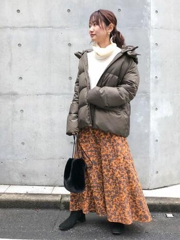 オレンジ系の鮮やかなフレアロングスカートに、カーキブラウンのアウターを羽織って見た目にもあたたかなコーデに。寒さの厳しい日でも、足元をパンプスに履き替えれば綺麗めにも着こなせるコーデです。