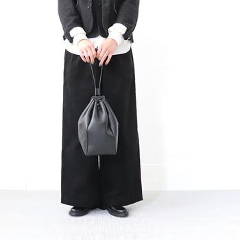 キャンバス生地にパラフィン加工が施された、ころんとまあるい巾着バッグ。口が大きく開くので、荷物の出し入れも楽チンです。