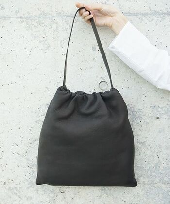 巾着型のブラックバッグはトレンド感を大切にしながらも、毎日持てるシンプルさ。柔らかな革素材の巾着バッグは、エレガントな中にも少しの抜け感が。