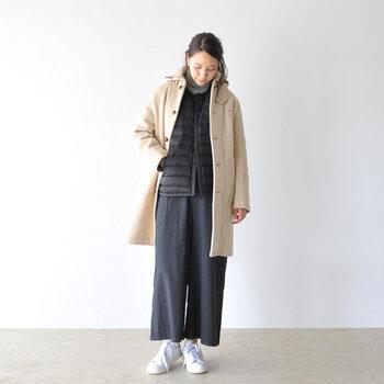 黒のインナーダウンジャケットを、ベージュのコートに重ねたスタイリング。ネイビーのワイドパンツに白スニーカーを合わせて、足元に爽やかなアクセントカラーをプラスしています。