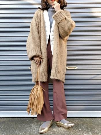毎シーズン大人気の、ユニクロダウンベストを使ったフェミニンな冬コーデ。タートルネックに白のインナーダウンをプラスして、さらに上からベージュのニットコートを羽織ったスタイリングです。ブラウンカラーのワイドパンツで、今年らしさ抜群のコーディネートに。