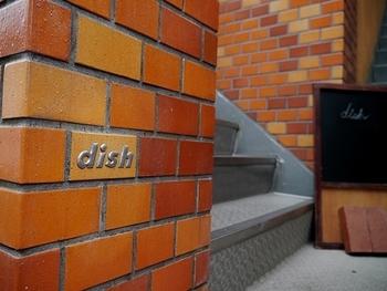 代々木上原駅の南口2番出口から歩いて約1分のところにある「dish-tokyogastronomycafe(ディッシュ トウキョウガストロノミーカフェ)」。レンガ色のビルの2Fにあります。お洒落なロゴが入った壁を発見して、入り口からワクワク!