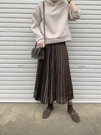 一言に「茶色」と言っても色合いはさまざま。こちらは、くすみ感が大人っぽい、こげ茶色のロングプリーツスカート。カジュアルなフーディと組み合わせれば、大人のスポーツミックスコーデが楽しめます。