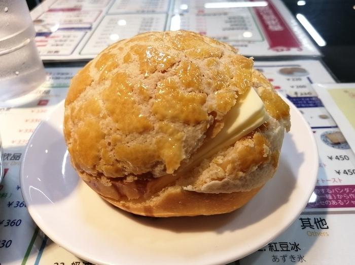 """""""香港版メロンパン""""と呼ばれる「ポーローパオ」も食べてみたいスイーツ。表面のクッキー生地はサクサクで、中のパン生地はふんわりやわらか。温かいパンに冷たいバターを挟んでいただくと、その豊かな風味に思わず笑みがこぼれます。"""