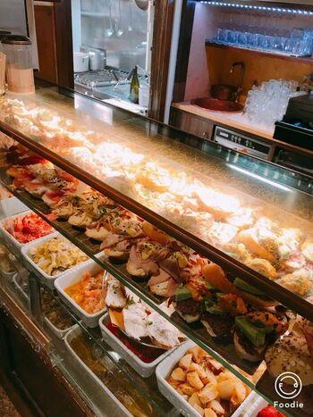 ショーケースに総菜などが並んでおり、バーカロの形態に近いですが、しっかりお腹を満たす食事を楽しめます。  立ち飲みを楽しめるカウンターと、落ち着いて食事できる座れる席もありますよ。  魚もお肉料理も人気ですが、食べてみてほしいおすすめは、パスタ。イカスミパスタやムール貝入りパスタなど、新鮮なシーフードを使った料理を、どうぞ召し上がれ。