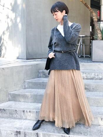 暗くなりがちな冬コーデですが、インナーに明るさがあると、春を先取りさせる着こなしが楽しめます。軽やかなスカートとブーツで、季節の変わり目を感じる絶妙バランスなコーデです。