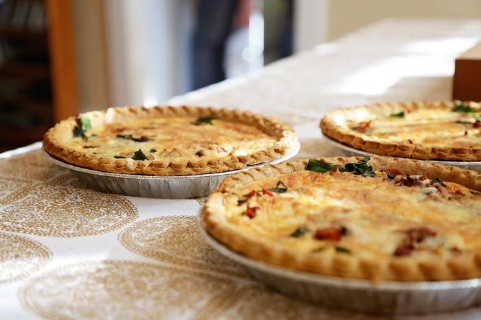 キッシュとは、卵と生クリームを使って作るフランスの郷土料理。パイ生地・タルト生地で作った器の中に、卵、生クリーム、ひき肉や野菜を加えて、チーズをたっぷりのせオーブンで焼き上げたもの。見た目が華やかで、テーブルがワンランクアップするため、おもてなしやホームパーティーにぴったりです。野菜が主役のもの、お肉やシーフードがメインのもの、パイ生地を使用せず他のもので代用したお手軽キッシュの作り方をご紹介します。