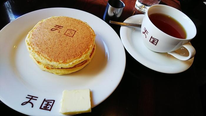 看板メニューのホットケーキ。オーダーを受けてから混ぜ合わせる小麦粉は2種類をブレンドし、銅板で焼いているので熱が均一に伝わって焼きムラができにくいのが特徴。「天国」の焼印もユニークで、添えられた四角いバターが懐かしい雰囲気です。