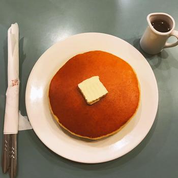 こんがりキツネ色のホットケーキは、王道の味。ナイフを入れるのがもったいないほど美しい焼き上がりです。まん丸のホットケーキが2枚重ねで、食べごたえも十分。