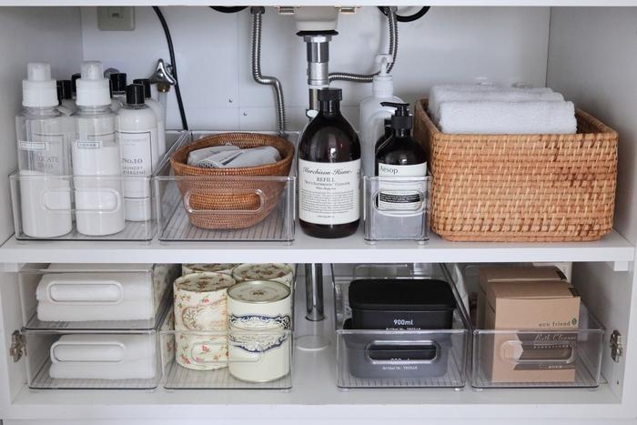 モノが溢れがちな洗面所。生活感と上手く付き合うためには、置くモノを「厳選する」ことが大切です。気になるものは扉付の収納にしまうか、カゴを使った収納を徹底するなど「隠す収納」を意識してみてください。  こちらのお宅は、透明のケースを使っているので何がどこにあるのか一目瞭然。 ボトルの洗剤類、洗顔料やハンドソープ、タオルなどアイテムごとに仕分けしています。 詰め替えタイプのレフィルなどは、派手なパッケージが多いため、透明ボトルに詰め替えてのだそう。