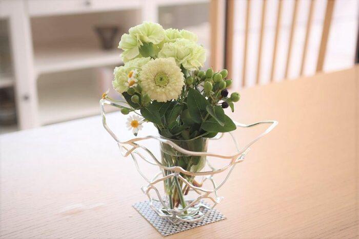 大きめのワイヤーバスケットやカゴなどを使って、ガラスの花瓶を包みこむように組み合わせれば、オリジナリティのある飾りかたに。ダイニングテーブルの上やリビングのキャビネットのうえ、玄関など個性的な飾りかたで楽しみたい場所に取り入れてみては。