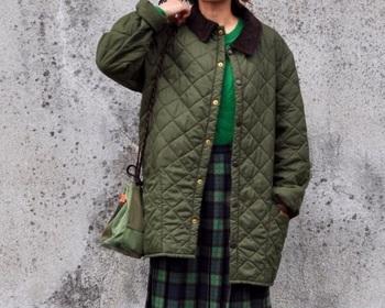 グリーンのタータンチェックスカートと合わせたのはバブアーのキルティングジャケット。英国トラッドスタイルのお手本といえそうなコーデです。
