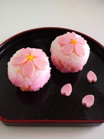 和菓子のように可愛らしい手まり寿司。魚肉ソーセージを型抜きして桜の花の飾りを作ります。