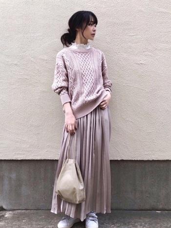 淡いピンクのケーブルニットに光沢感のあるプリーツスカートを合わせた大人可愛いコーデ。襟元に覗かせた白のフリルや白スニーカー、白バックなど、ピンクとホワイトの2色で全体をまとめることでおしゃれ感が極まります。