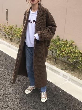今年らしいビッグシルエットのブラウンのコートで、カジュアルな白トレーナとデニムのスタイルを大人っぽくアップデート。