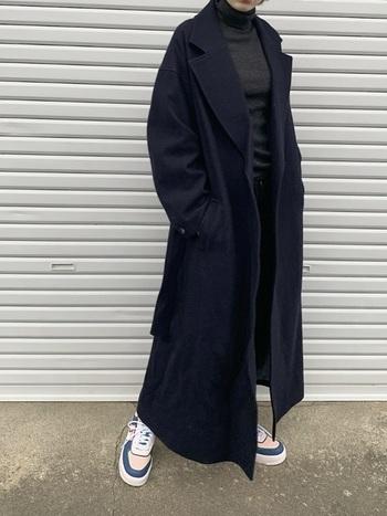 紺色のスーパーロングコートにチャコールグレーのインナーでクールにまとめたスタイル。足元に明るめのスニーカーをチョイスして、抜け感を加えることで、マキシ丈とダークトーンの重さを軽減しています。