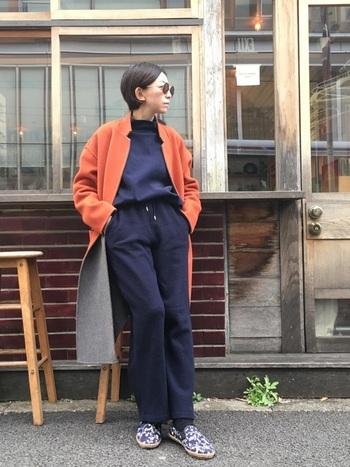 上下を紺色で統一したカジュアルワントーンコーデに、オレンジ色のロングコートを羽織ったスタイリング。インナーを縦長ラインを作り、色のコントラストを強調した新鮮な印象です。