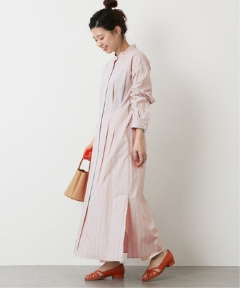 乳白色のピンクのストライプシャツワンピースには、白いパンツを重ね、柿色の靴を合わせれば、素敵なグラデーションコーデに。軽やかさを出したいならヘアスタイルはアップできまり。