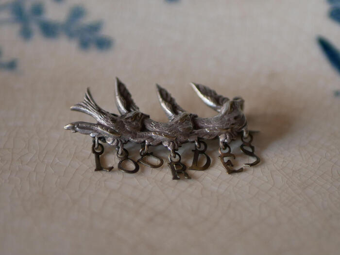 「LOURDRES」という文字を運んでいるようにも見えるツバメのブローチです。「LOURDRES」はフランスの地方都市の名前。そっとブローチに触れたら、遠い国とのご縁を感じます。