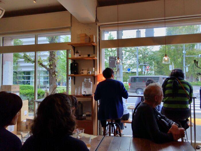 通りを広く見渡せる明るい店内には、思い思いの時間を過ごすお客さんの姿が。同じ空間を共有しながら大人の距離感を保てる、居心地の良い雰囲気に満ちています。