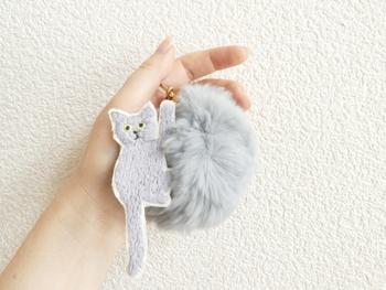 手刺繍の猫とフェイクファーのポンポンが組み合わさったバッグチャーム。まるで毛糸玉で遊ぶ姿のような無邪気さを感じます。バッグに限らず、鍵やパスカードホルダーなどお気に入りのものに付けてみてください。