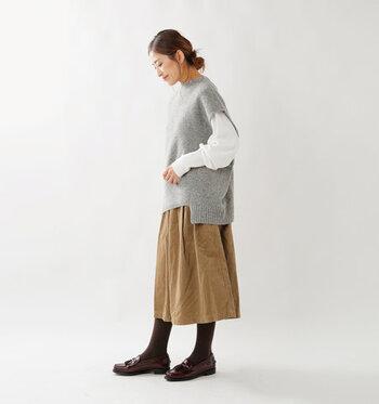 コンパクトなグレーのニットトップスに、白のプルオーバーをレイヤードした着こなしです。キャメルカラーのスカートとブラウンのローファーで、落ち着いた雰囲気が魅力的なナチュラルコーデに。