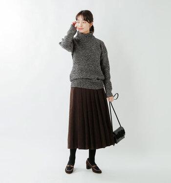 濃いグレーのハイネックニットに、ブラウンのプリーツスカートを合わせたコーディネートです。全体をグレーやブラウン系のダークトーンで揃えて、カジュアルガーリーな着こなしを大人コーデに格上げしています。
