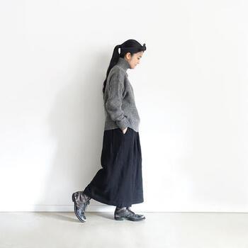 グレーのタートルネックニットに、ネイビーのロングスカートを合わせたベーシックなコーディネートです。ゆったりシルエットでナチュラルな印象にまとめつつ、足元にはメンズライクなブーツをチョイス。バランス感を重視した、大人コーデに仕上げています。