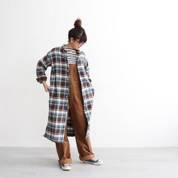 厚手の生地のチェック柄ワンピースを、羽織りとして使用したコーディネート。カジュアルなブラウンのオーバーオールコーデを、今っぽくアップデートしています。