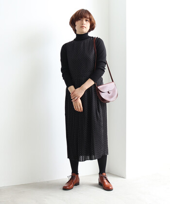 ドット柄のワンピースに、黒のタートルネックを合わせて1枚のワンピースのようにスタイリング。ブラウンのショルダーバッグとシューズで軽さをプラスして、ドット柄を大人っぽく着こなしています。