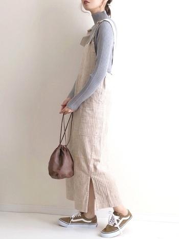 コーデュロイ素材のジャンパースカートをリブのハイネックで大人っぽく仕上げ、足元のスニーカーでハズシを利かせたスタイル。くすみカラーでまとめていて雰囲気のある着こなしになっています。