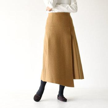 Aラインのふわっと広がるシルエットで、女性らしい印象を与えるラップスカートです。ふっくらとしたメルトン素材を使用し、寒い季節にぴったりな温もりのあるアイテムに仕上げています。
