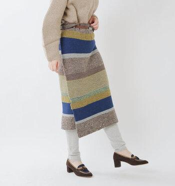 さまざまな糸を使用して、ボーダー柄を描いたニット素材のラップスカートです。すっきりしたシルエットで、レギンスやボトムスと合わせてもサマになるのがポイント。民族チックな表情で、個性のある着こなしを演出してくれます。