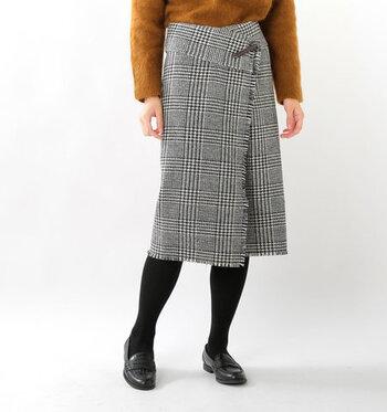 加工を一切施していない素朴な素材感が魅力の、ハリスツイード生地を使って作られたラップスカート。付属のキルトピンでスカートを留める形になっていて、着るだけで上品な大人の着こなしが楽しめます。黒タイツとの相性も抜群な一枚です。