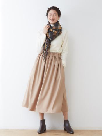 白のタートルネックを、ベージュのスカートにタックイン。無地同士の着こなしがシンプルになりすぎないよう、チェック柄のストールで顔周りにアクセントをプラスしています。足元は、ブラウンのショートブーツで季節感たっぷりに。