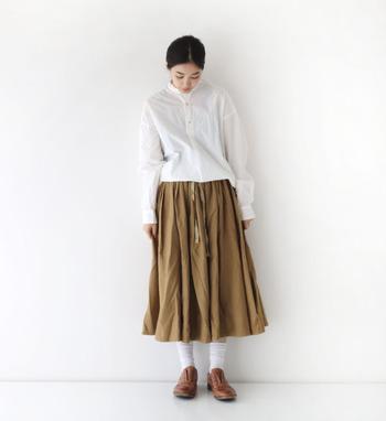 白のチュニックトップスに、濃いベージュのスカートを合わせた着こなしです。トップスをゆるくタックインして、きっちり感が出すぎないようまとめています。白ソックスとブラウンのシューズが、大人女子にぴったりなナチュラルさを演出。