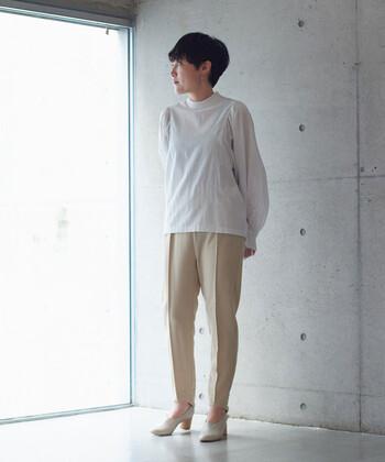 白のハイネックブラウスに、ベージュのセンタープレスパンツを合わせたキレイめな着こなし。足元もヒールのあるパンプスで、オフィスカジュアルとしても活用できる優秀コーデの完成です。