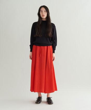 黒のニットトップスに鮮やかな赤のロングスカートを合わせて。ビビッドな色でもスカートなら意外と合わせやすいのでおすすめ。単色同士の組み合わせもおしゃれに仕上がります。