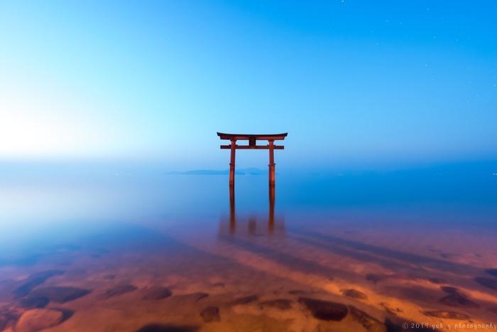 日本最大の湖である琵琶湖にそびえたつ、白鬚神社の「湖中大鳥居」。鳥居越しにぼんやりと見えるのは、琵琶湖最大の島「沖の島」です。白鬚神社は近江最古の神社で、全国にある白髭神社の総本社でもあります。