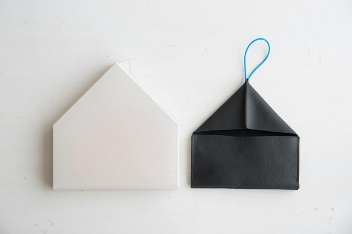 「toe to knee」の長財布は、ユニークなシルエットが特徴。小銭の取り出しやすさを考えた作りで、ゴムひもを外してフタを開けると2つの仕切りが大きく開きます。これが小銭を取り出しやすい仕組み。