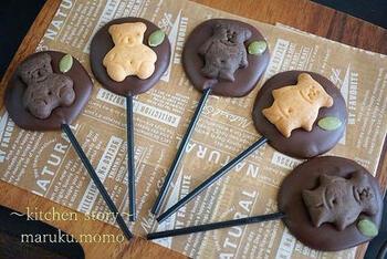 溶かした板チョコをクッキングペーパーの上で成形し、棒と飾りをつけて冷やし固めるだけの簡単レシピ。油を加える一工夫によって、板チョコでもなめらかな口どけに仕上がります。かわいいビスケットで飾り付けすれば、ぶきっちょさんでも簡単にかわいく作ることができますよ♪