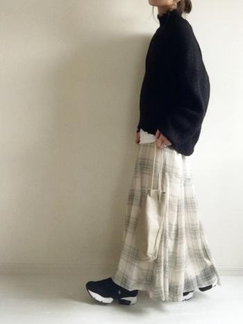 重く見えがちな黒いタートルネックニットも、透け感のあるチェックのフレアロングスカートを合わせれば「真冬感」を脱却できます。足元は黒いスニーカーで統一感を。