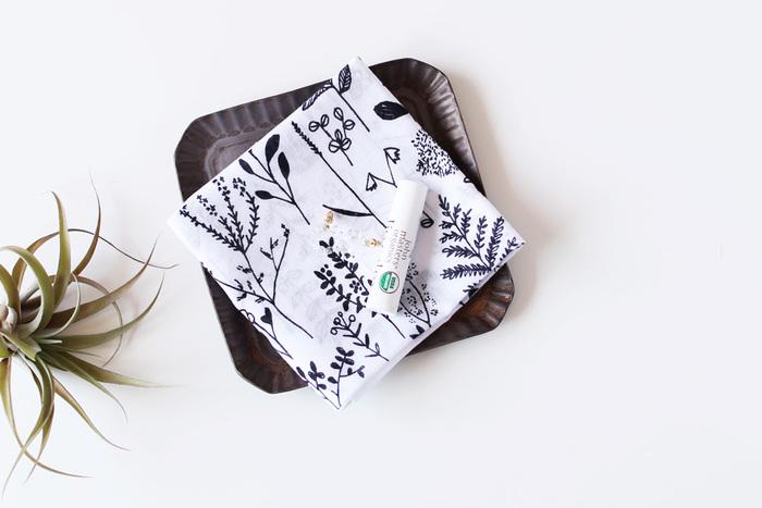 パリッとハリのあるコットン素材のハンカチ。白地に黒のモノトーンで描かれた草花がスタイリッシュかつ清楚です。
