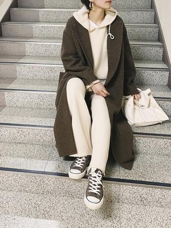 ブラウン系のチェック柄ロングコートに白パーカーを合わせた着こなしは、首元からフードを出すことでラフな印象をプラス。ボトムスとバッグを白で統一することで、きれいめカジュアルに仕上がります。