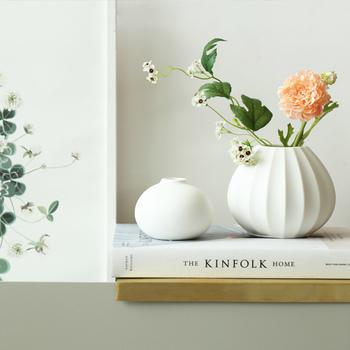 コロンと可愛いフォルムと透き通るような白さが素敵な花瓶。花を挿しても挿さなくても、インテリアのアクセントになっています。  複数並べたいときには、素材感を合わせることが調和するコツです。  素材感が同じでデザインやサイズが異なる花瓶を並べると、より奥行きのあるインテリアに仕上がります。