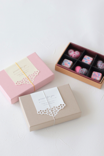 箱に1粒ずつ並べてラッピングしたら、市販のバレンタインチョコのような見栄えに。リボンをかけるのではなく、レースのヘッダーシールと紐で仕上げればフェミニンな雰囲気のかわいいラッピングに仕上がりますよ。
