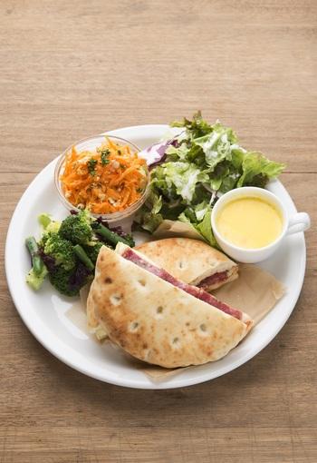 野菜をたっぷり使った、栄養満点のメニューが人気です。写真はフォカッチャサンド。モッツァレラチーズとミラノハム、トマト、バジルソースを挟んだ一品です。サラダやスープも付いて、彩りもボリュームも◎