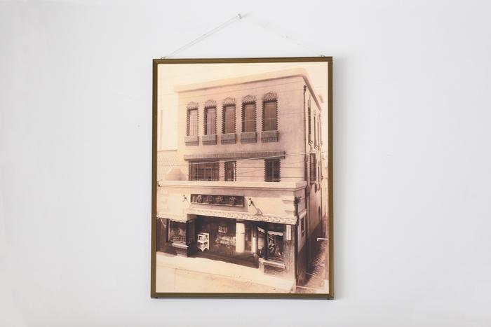 玄関には、薬局だったころの写真が飾られている。当時でも飛びぬけてモダンな建物だったに違いない