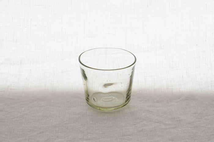 胡桃の殻を燃やした灰を、ガラスの原料として使っている「くるみガラス」のそば猪口です。一見するとシンプルな透明の器に見えますが、よく見ると淡いグリーンが溶け込んでいるのがわかります。ひとつひとつ手づくりで作っているので、同じ商品でもそれぞれ違う表情に仕上がっているのが魅力的ですね。