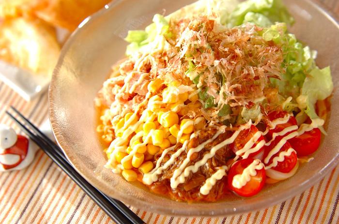 """これさえあれば、ワンプレートで大満足できるサラダうどんのレシピ。レタスやプチトマト、缶詰のコーン、ツナをたっぷり乗せましょう。茹でたうどんをお皿に盛って、あとはトッピングを乗せていくだけ。特別なつゆ作りの必要もありません。えのきの漬物""""なめたけ""""とめんつゆ、マヨネーズ、かつお節をかければ完成です。よ~く混ぜていただきましょう♪"""